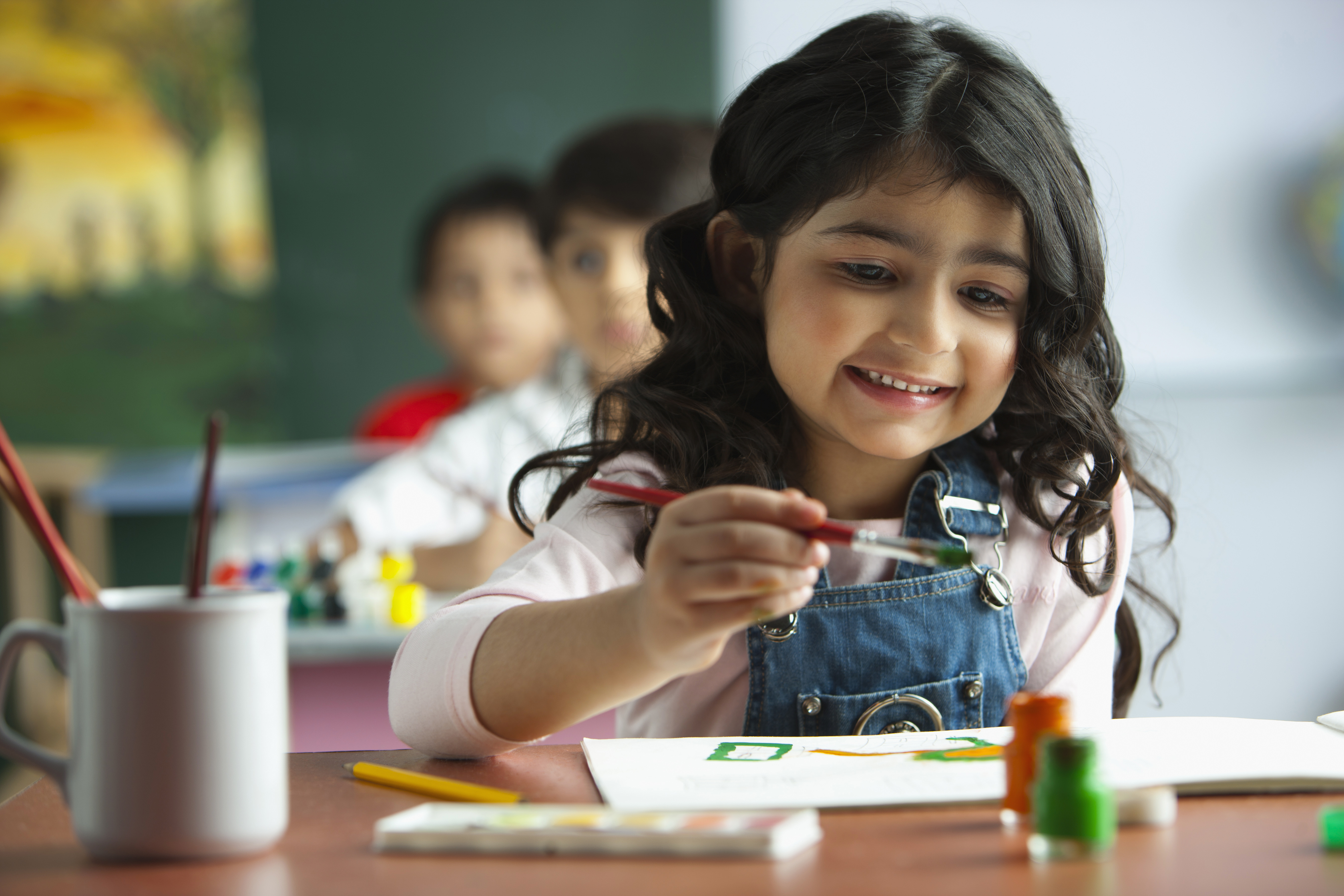 Smiling child with paintbrush in classroom
